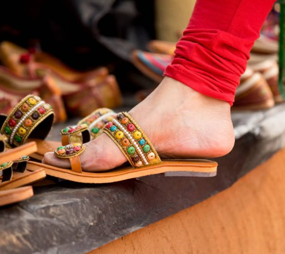 Indian women shopping for traditional footwear at street market